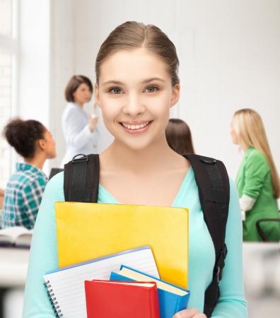 profesor alumno: Chica estudiante feliz con mochila y cuadernos en la escuela