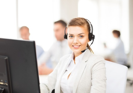 friendly female helpline operator with headphones in call centre Stock Photo
