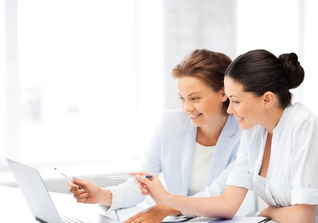 two smiling businesswomen working with laptop in office