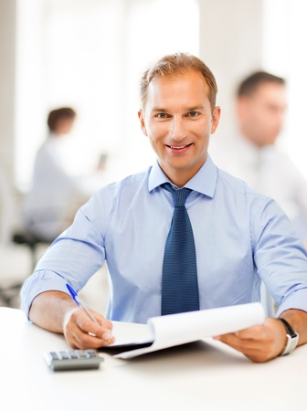 analytical: middle-aged businessman with notebook and calculator in office Stock Photo