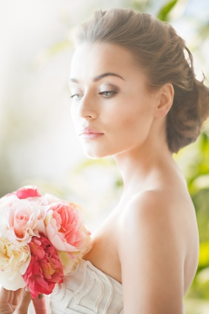 bridal dress: wedding and beauty concept - young woman with bouquet of flowers