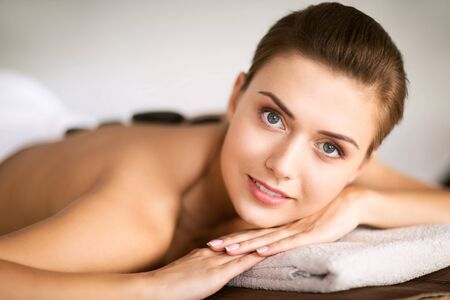holidays and spa concept - beautiful woman in spa salon with hot stones photo