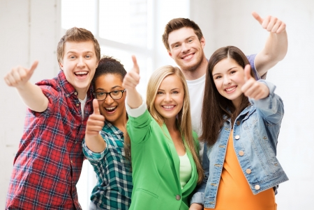 approved: education concept - happy team of students showing thumbs up at school Stock Photo