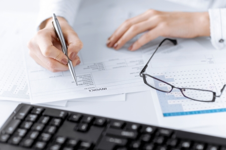 bookkeeping: picture of woman hand filling in invoice paper Stock Photo