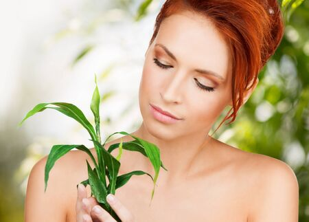 beauty and eco cosmetology concept - beautiful woman on nature with green sprout photo