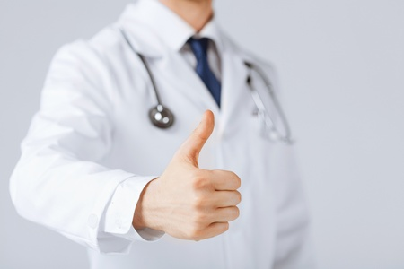 close up of male doctor hand showing thumbs up photo