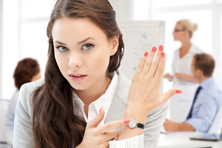 business and time management concept - businesswoman pointing at her watch photo