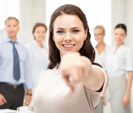 concept d'entreprise - jolie jeune femme d'affaires pointant vers vous dans le bureau