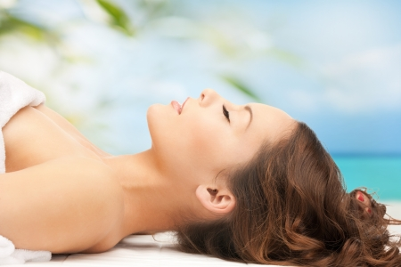 health resort treatment: beauty and spa concept - woman in spa lying on the massage desk