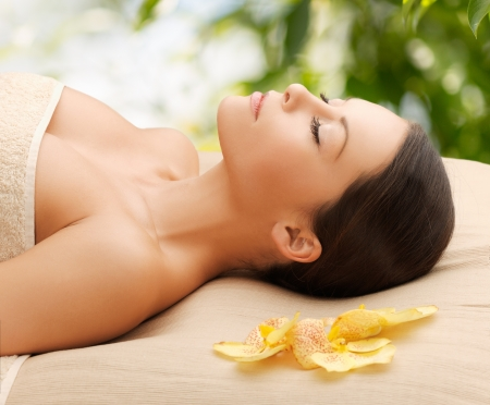 spa and holidays concept - woman in spa lying on the massage desk photo