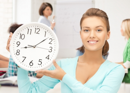 education and time management - attractive student pointing at clock photo