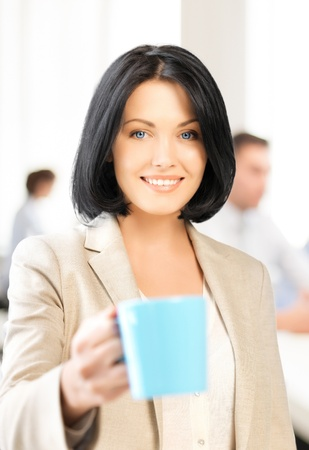 business concept - beautiful businesswoman with cup of coffee photo