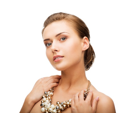 string of pearls: beautiful woman wearing statement necklace with pearls