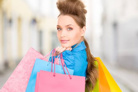 shopping and tourism concept - beautiful woman with shopping bags in ctiy Stock Photo - 21034336