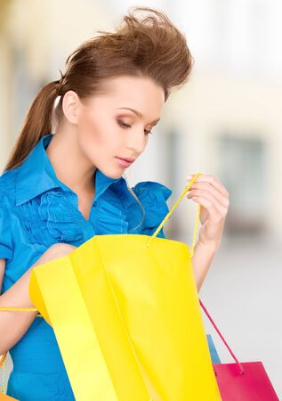 shopping and tourism concept - beautiful woman with shopping bags in ctiy Stock Photo - 21034337