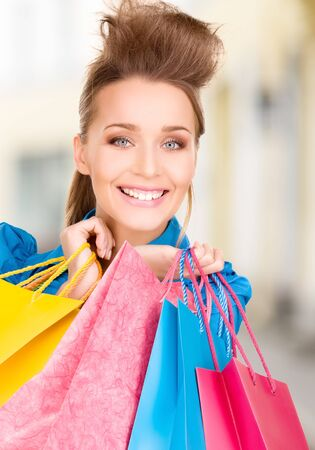 shopping and tourism concept - beautiful woman with shopping bags in ctiy Stock Photo - 21034338