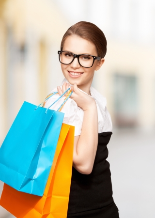 shopping and tourism concept - beautiful woman with shopping bags in ctiy Stock Photo - 21034347