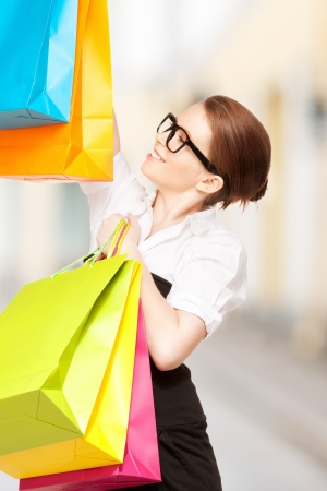 shopping and tourism concept - beautiful woman with shopping bags in ctiy photo