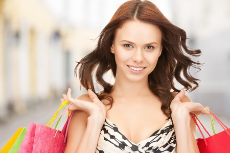 shopping and tourism concept - beautiful woman with shopping bags in ctiy Stock Photo - 21034365
