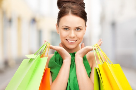 shopping and tourism concept - beautiful woman with shopping bags in ctiy Stock Photo - 21034366