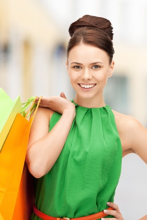 shopping and tourism concept - beautiful woman with shopping bags in ctiy Stock Photo - 21034367