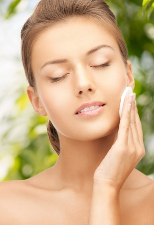 beauty and eco cosmetology concept - beautiful woman with cotton pad photo