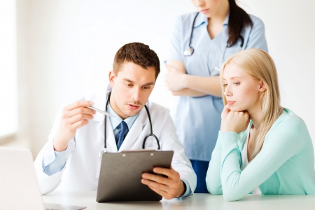 serious doctor: healthcare and medical concept - doctor and nurse with patient in hospital