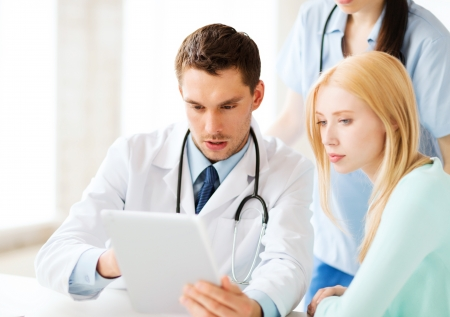 diagnosis: healthcare, medical and technology - doctor showing something patient on tablet pc in hospital Stock Photo