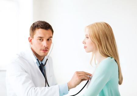 doctor's appointment: healthcare and medical - doctor with stethoscope listening to the patient in hospital Stock Photo