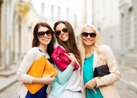 holidays and lifestyle concept - beautiful girls with bags in the ctiy photo