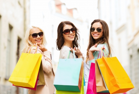 shopping and tourism concept - beautiful girls with shopping bags in ctiy Reklamní fotografie - 21034485