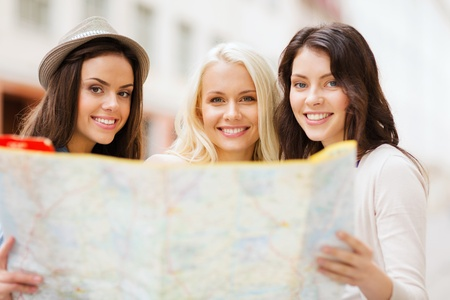 tours: holidays and tourism concept - beautiful girls looking into tourist map in the city Stock Photo