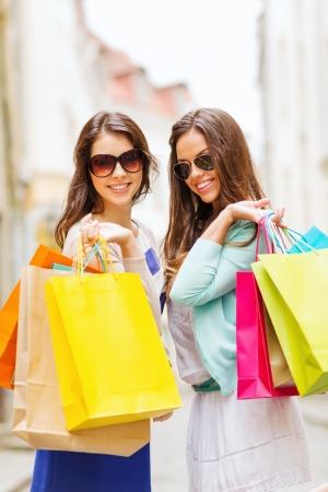 chicas comprando: compras y concepto de turismo - hermosas chicas con bolsas de la compra en ctiy