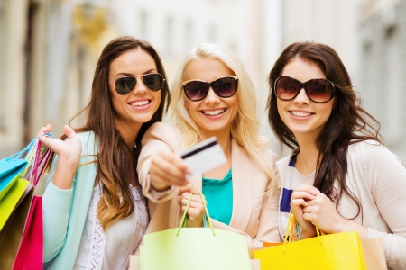 gifts: shopping and tourism concept - beautiful girls with shopping bags and credit card in ctiy