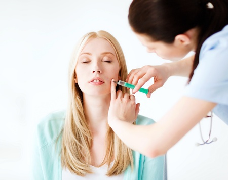 nurse injection: healthcare, medical and plastic surgery - beautician with patient doing botox injection in hospital Stock Photo