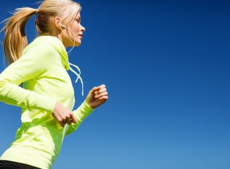escucha activa: el deporte y el concepto de estilo de vida - mujer que hace correr con auriculares al aire libre
