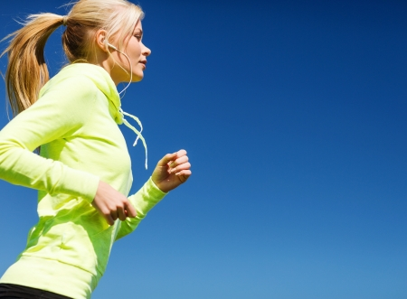 sport and lifestyle concept - woman doing running with earphones outdoors photo