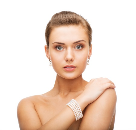 string of pearls: beauty and jewelery concept - beautiful woman with pearl earrings and bracelet