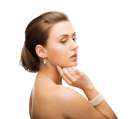bangle: beauty and jewelery concept - beautiful woman with pearl earrings and bracelet