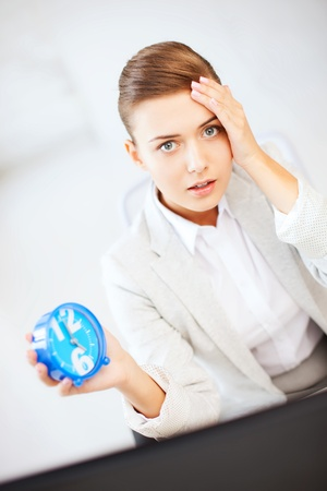 business and time management concept - stressed businesswoman holding clock photo