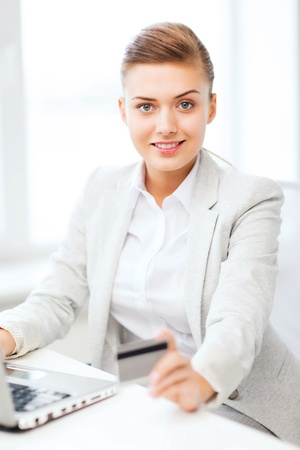 internet banking: business and internet concept - smiling businesswoman with laptop using credit card Stock Photo