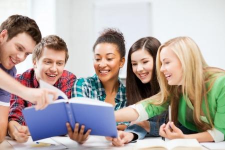 onderwijs concept - groep studenten leesboek op school