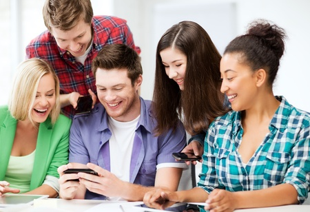 education, technology and internet - smiling students looking at smartphone at school photo