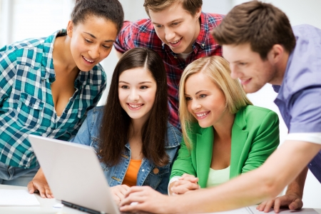 university classroom: education and internet - smiling students looking at tablet pc in lecture at school Stock Photo