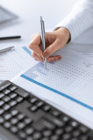 picture of woman hand writing on paper with numbers