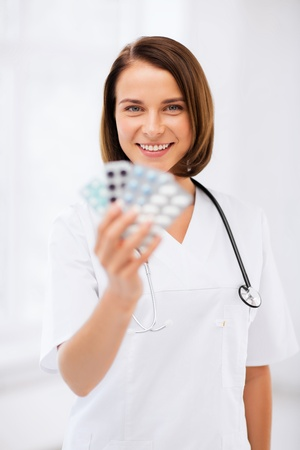 healthcare and medical concept - doctor with blister packs of pills photo