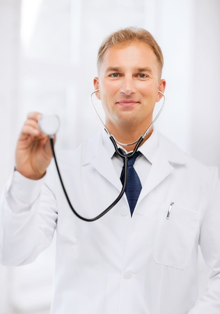 healthcare and medical concept - young male doctor with stethoscope photo