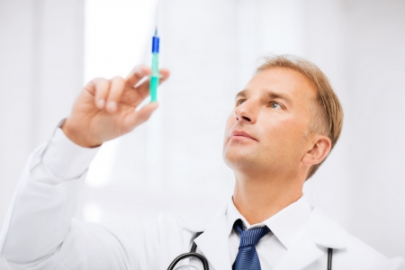 insulin syringe: healthcare and medical concept - male doctor holding syringe with injection
