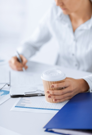 business concept - businesswoman with coffee filling in blank paper photo