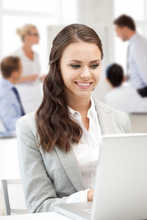business and communication concept - businesswoman with laptop computer at work Stock Photo - 21089406